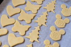 La fine su della pasta del biscotto nelle forme differenti si trova sullo shee di cottura Fotografia Stock