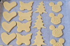 La fine su della pasta del biscotto nelle forme differenti si trova sullo shee di cottura Immagini Stock