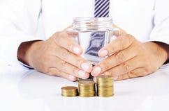 La fine su della pila delle monete dei soldi con l'uomo di affari passa il gl della tenuta immagine stock libera da diritti