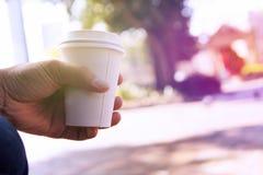 La fine su della tenuta maschio della mano porta via la tazza di caffè al Ti di mattina Fotografia Stock