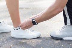 La fine su delle coppie di amore lega la scarpa affinchè l'amica sia pronta per un esercizio nel parco Immagini Stock Libere da Diritti