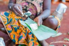 La fine su delle mani africane della donna che riempiono il plantano va con manioca per rendere a traditonal baton de manioc came immagini stock