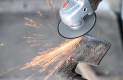 La fine su di un uomo affila un'ascia facendo uso della smerigliatrice elettrica immagini stock