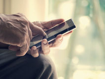 La fine su di un uomo anziano è soddisfatta della battitura a macchina dello Smart Phone a macchina mobile Immagine Stock