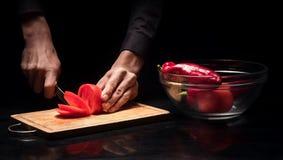 La fine su di uomo le mani che tagliano il pomodoro a pezzi su fondo nero Fotografie Stock