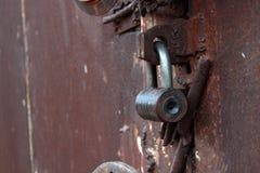 La fine su grande metallo ha arrugginito porte del garage chiuse a chiave fotografia stock libera da diritti