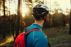 La fine su ha sparato dalla parte posteriore di giovane ciclista barbuto bello dell'uomo che indossa il casco protettivo, la magl immagini stock