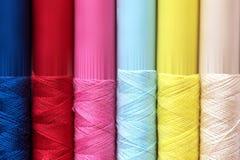 La fine su multi colore dei fili delle bobine rotola come fondo Immagini Stock