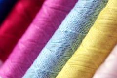 La fine su multi colore dei fili delle bobine rotola come fondo Fotografia Stock