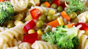La fine su pasta a spirale con le verdure su un piatto gira su un fondo nero archivi video
