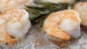 La fine su sull'gamberetti frigge su una padella con un aglio e un rosmarino video d archivio