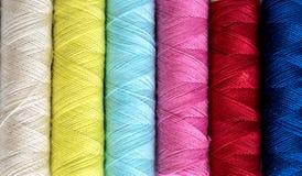 La fine su un multi colore dei fili delle bobine rotola come fondo Fotografia Stock Libera da Diritti