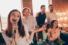 La fine sui compagni dei migliori amici della foto la riunione di karaoke che va in giro le canta le sue signore la solista lui l immagine stock libera da diritti