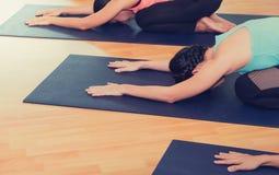 La fine sul gruppo di persone che fanno il ` s del bambino di yoga posa in trai dello studio Fotografia Stock