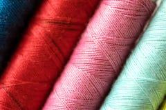 La fine sul multi colore dei fili delle bobine rotola come fondo Immagini Stock Libere da Diritti