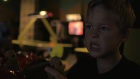 La fine sul punto di vista del bambino piccolo sta giocando il video videogioco arcade nel centro del gioco stock footage