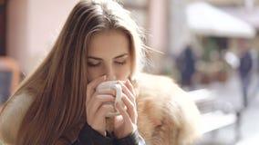 La fine sul ritratto della ragazza astuta beve una tazza di cottura a vapore del caffè 4K stock footage