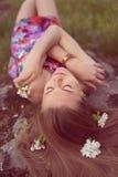 La fine sul ritratto di bella giovane donna bionda che mette sulla pietra con i fiori nel suo closing dei capelli osserva il sogn Immagini Stock Libere da Diritti