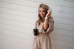 La fine sul ritratto di una ragazza sorridente nella tenuta del cappello porta via la tazza di caffè all'aperto immagini stock libere da diritti