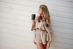 La fine sul ritratto di una ragazza sorridente nella tenuta del cappello porta via la tazza di caffè all'aperto fotografie stock libere da diritti