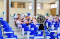 La fine sul supporto del microfono sulla tavola nella conferenza ed il fondo offuscano la sala riunioni interna di seminario Fotografie Stock
