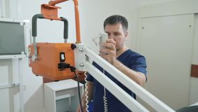 La fine sull'uomo adulto in vestiti medici regola l'apparecchiatura di raggi x Medico nell'ospedale lavora con attrezzatura medic stock footage