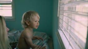 La fine sulla bella madre del ritratto tiene un figlio del bambino, grande finestra nei precedenti Immagini Stock Libere da Diritti