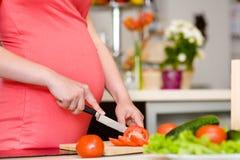 La fine sulla donna incinta con il coltello sulla cucina taglia il pomodoro Fotografie Stock