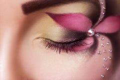 La fine sulla foto dell'occhio chiuso femminile con il fiore compone Immagine Stock