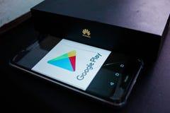 La fine sulla foto della scatola di Huawei con il logo di HUAWEI di cinese ed il logo di Google Play sullo smartphone fotografia stock libera da diritti