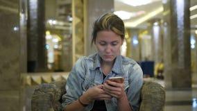 La fine sulla giovane donna caucasica in un rivestimento dei jeans utilizza uno smartphone, scrive i messaggi sulla rete sociale  stock footage