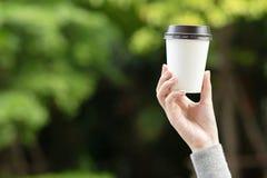 La fine sulla giovane mano femminile della gente che tiene la tazza di carta di porta via il caffè bevente fotografia stock libera da diritti