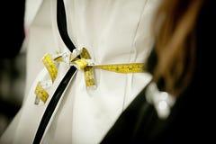 La fine sulla misura gialla avvolge il vestito bianco nello studio del progettista fotografia stock libera da diritti