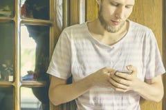La fine sulla persona di sesso maschile si appoggia il guardaroba ed usando telefono a casa d fotografia stock
