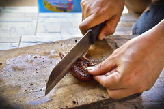 La fine sulle mani dei man's sta tagliando la carne arrostita su un taglio di legno Fotografie Stock Libere da Diritti
