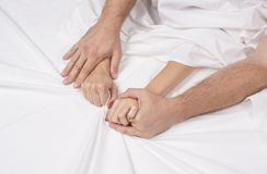La fine sulle mani di una coppia rende ad amore il sesso caldo su un letto immagine stock