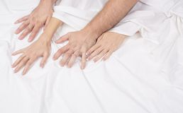 La fine sulle mani di una coppia rende ad amore il sesso caldo su un letto fotografie stock
