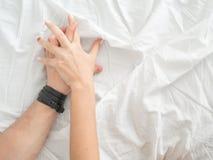 La fine sulle mani di una coppia rende ad amore il sesso caldo su un letto immagini stock libere da diritti