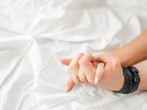 La fine sulle mani di una coppia rende ad amore il sesso caldo su un letto fotografia stock libera da diritti
