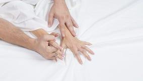 La fine sulle mani di una coppia rende ad amore il sesso caldo su un letto immagine stock libera da diritti