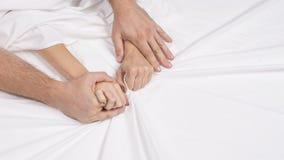 La fine sulle mani di una coppia rende ad amore il sesso caldo su un letto fotografia stock