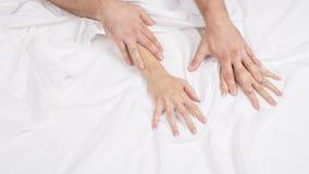 La fine sulle mani di una coppia rende ad amore il sesso caldo su un letto immagini stock
