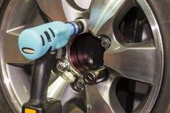La fine sullo strumento elettrico della chiave per l'assemblea o l'ONU installa la ruota di automobile al garage o all'officina fotografie stock libere da diritti
