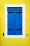La finestra blu shutters su una parete gialla della casa Immagine Stock Libera da Diritti