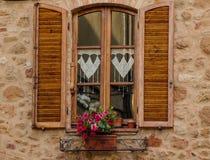 La finestra con i fiori e gli otturatori di legno Fotografie Stock