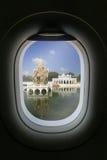 La finestra dell'aeroplano con l'attrazione della destinazione di viaggio scoppio Immagine Stock