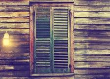 La finestra di cabina rustica con gli otturatori chiusi ed il portico si accendono Fotografia Stock