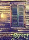 La finestra di cabina rustica con gli otturatori chiusi ed il portico si accendono Immagini Stock Libere da Diritti