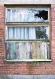 La finestra ha imbarcato su dai pannelli di legno in una vecchia casa con mattoni a vista rossa fotografia stock libera da diritti