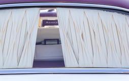 La finestra posteriore di un'automobile storica con una tenda crema Fotografie Stock